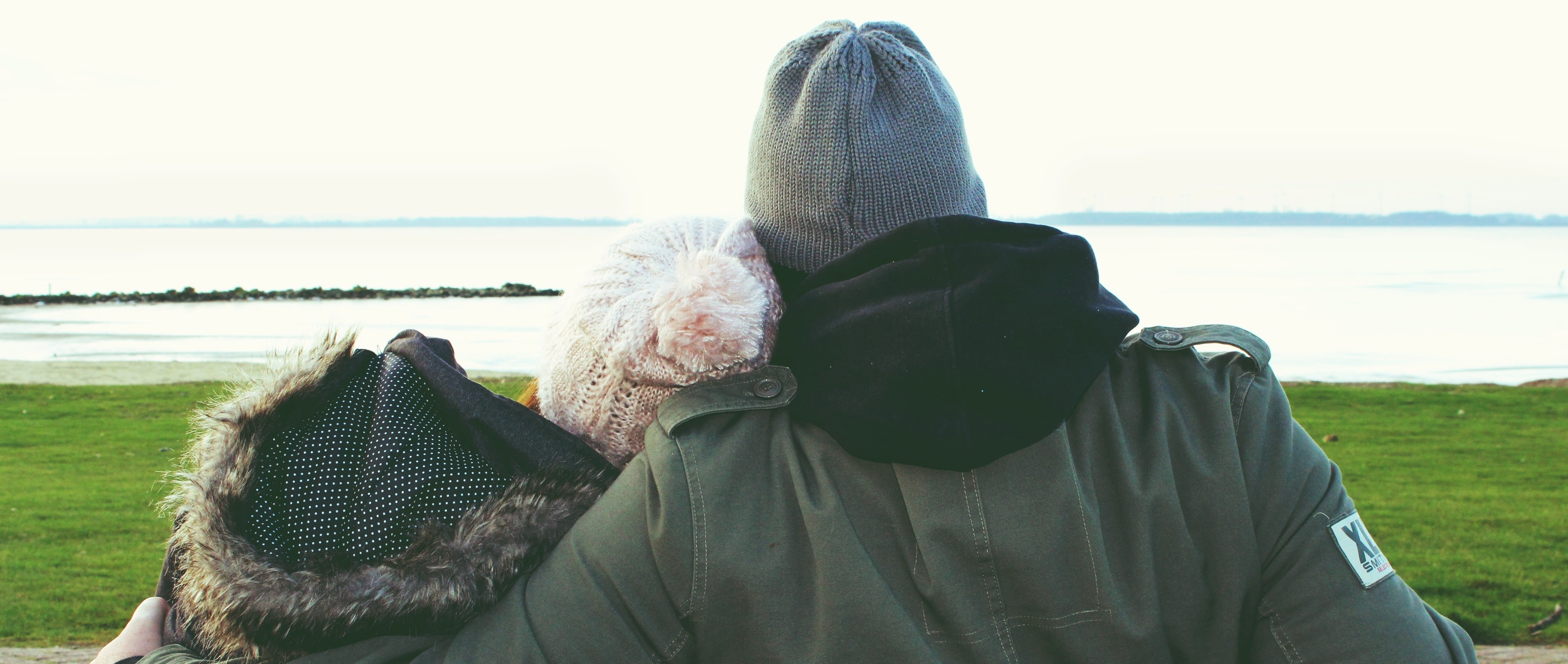 Back head shot of a man and woman in winter coats looking at a body of water while sitting on a bench.