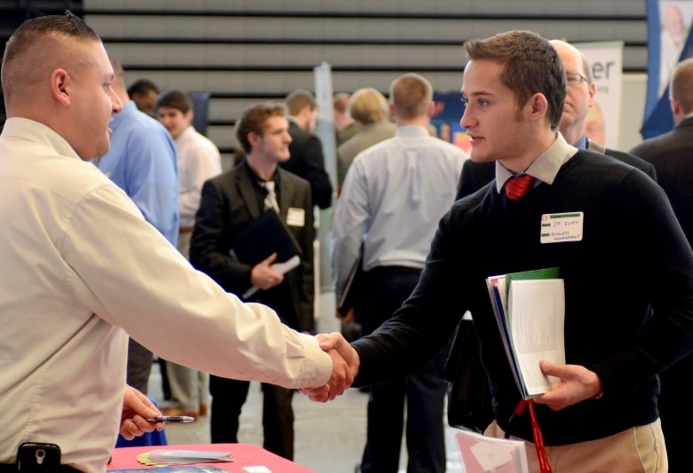 Students shaking hands at the Davenport career fair.