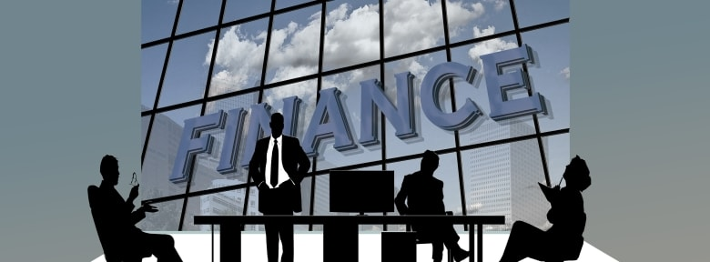Silhouette of four people at a desk with the word finance in the background.