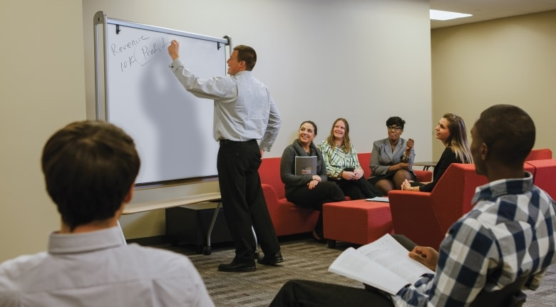 Davenport professor writing on a white board in his classroom with students.