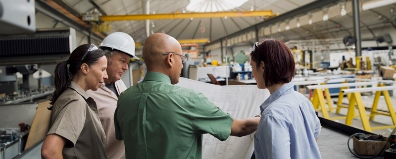 A production team looking at a blueprint in a factory.