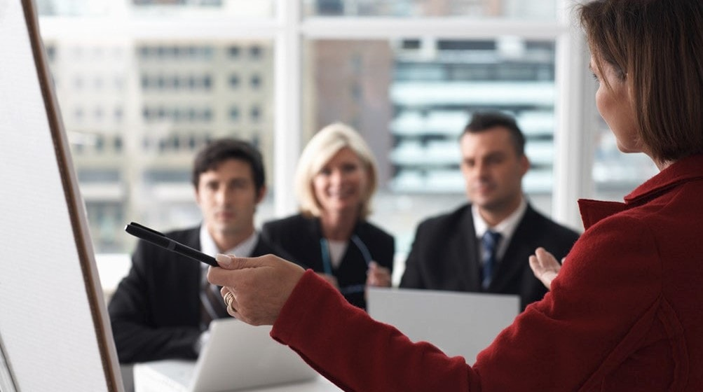 A woman holding a pen, pointing at an easel during a meeting with three other people.