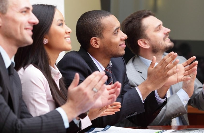 Four people clapping at a business event.