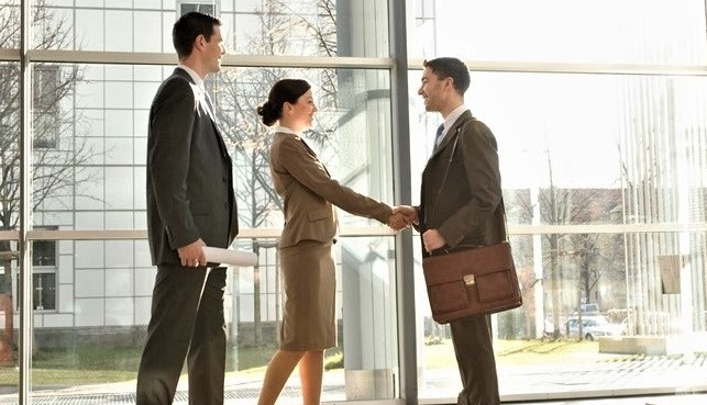 Two business men and one woman shaking hands at a business meeting.