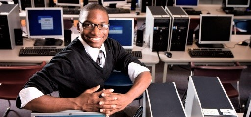 Young man sitting in a computer lab smiling and looking toward the audience.